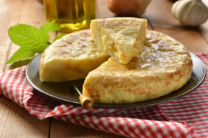 Spanish omelette with potato and egg accompanied by olive oil